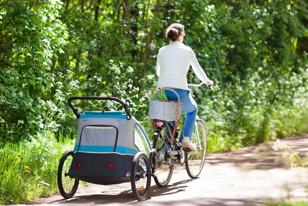 Image showing woman riding bike, biking with a baby carrier